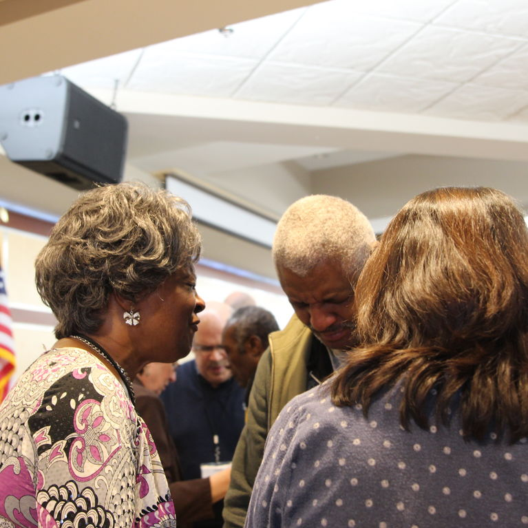 Guests and members of Madison Square Church praying together.